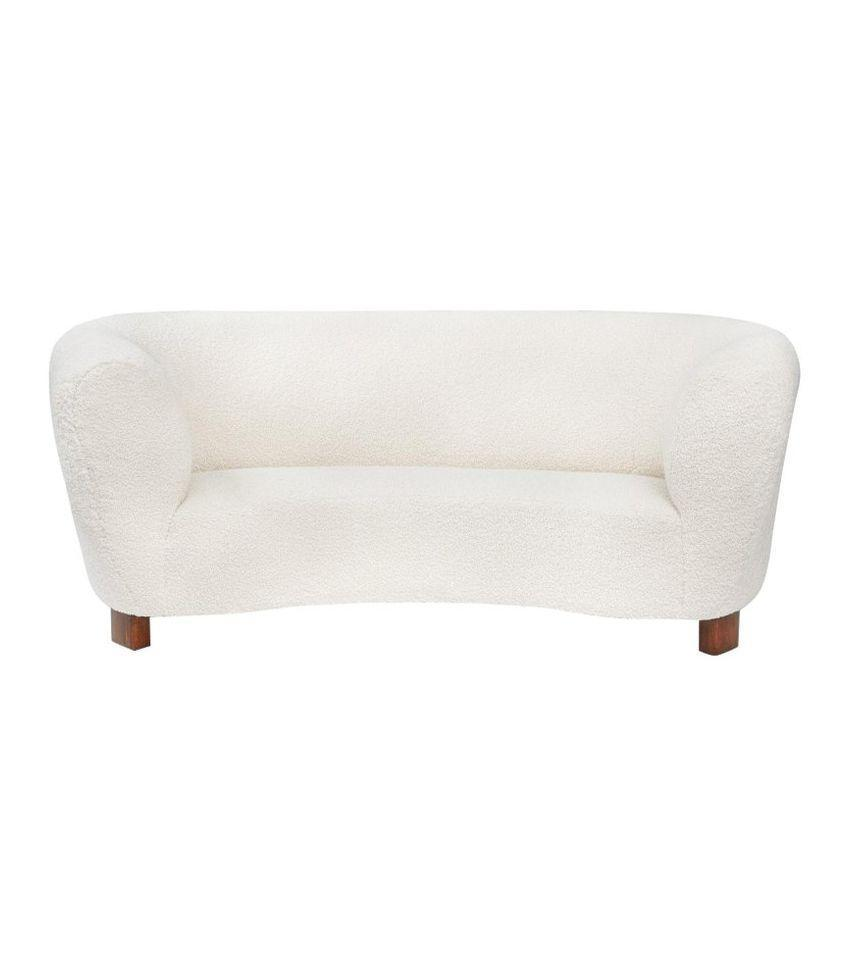 This round loveseat built in the 1940s has been reupholstered in bouclé fabric for an amazing vintage find.