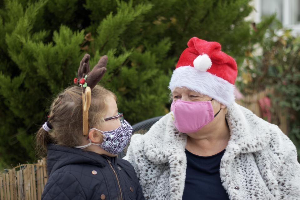 A happy  grandmother with her grandchild outside wearing reindeer antlers and a santa hat and protective face masks.
