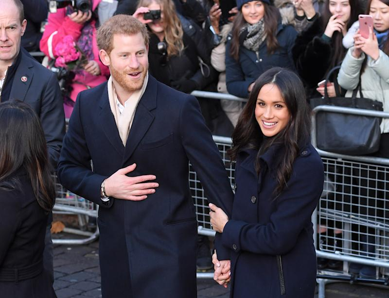 Meghan Markle grabs hold of Prince Harry's arm as they attend a royal visit
