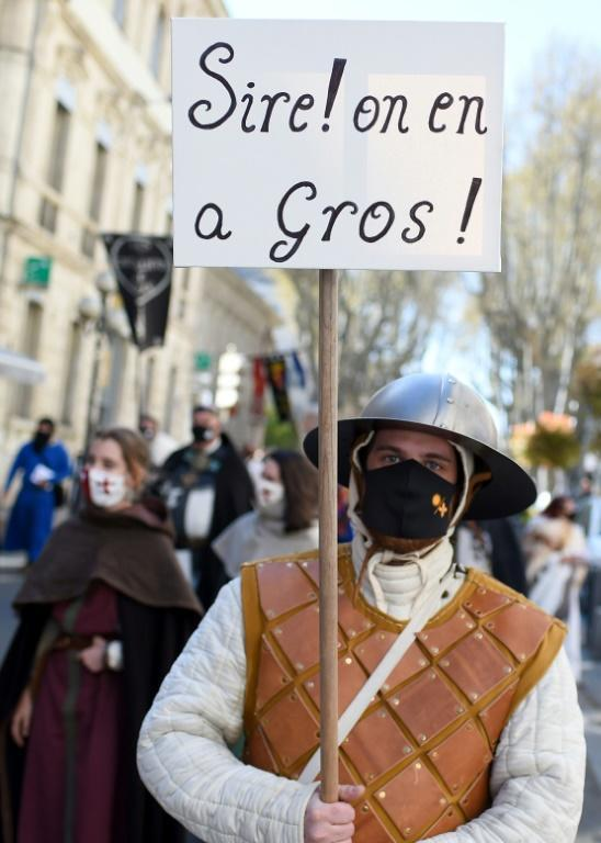 """A man wearing a period costume, holds a placard reading """"Sire! we are fed up"""" during a demonstration in southern France"""