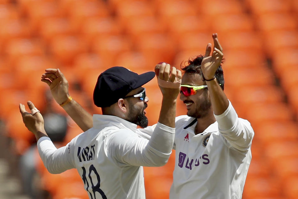 India's Axar Patel, right, celebrates with captain Virat Kohli after the dismissal of England's Ben Stokes during the third day of fourth cricket test match between India and England at Narendra Modi Stadium in Ahmedabad, India, Saturday, March 6, 2021. (AP Photo/Aijaz Rahi)