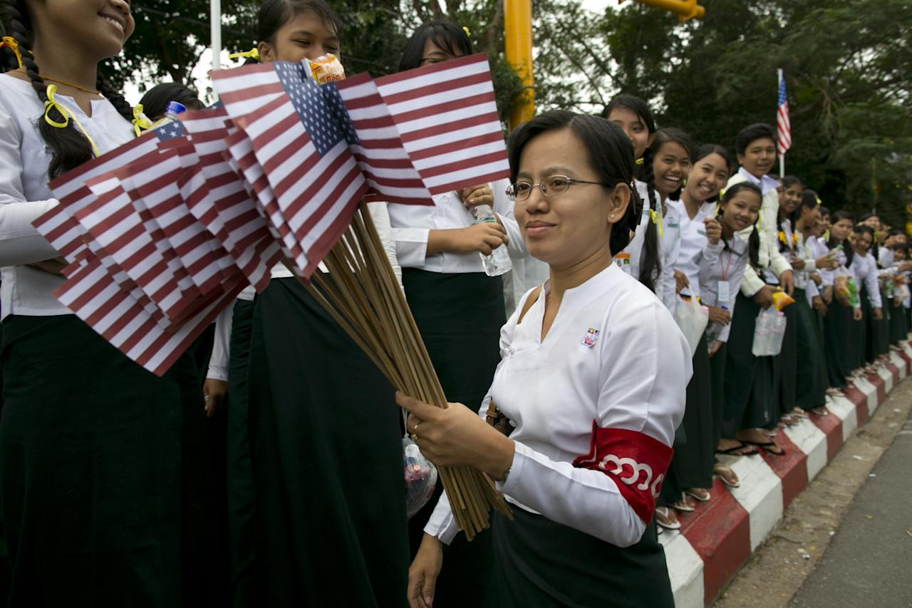 YANGON, MYANMAR - NOVEMBER 19:  A Burmese teacher holds American flags as students line the streets to welcome US President Barack Obama as arrives at Yangon International airport during his historical first visit to the country on November 19, 2012 in Yangon, Myanmar. Obama is the first US President to visit Myanmar while on a four-day tour of Southeast Asia that also includes Thailand and Cambodia. (Photo by Paula Bronstein/Getty Images)