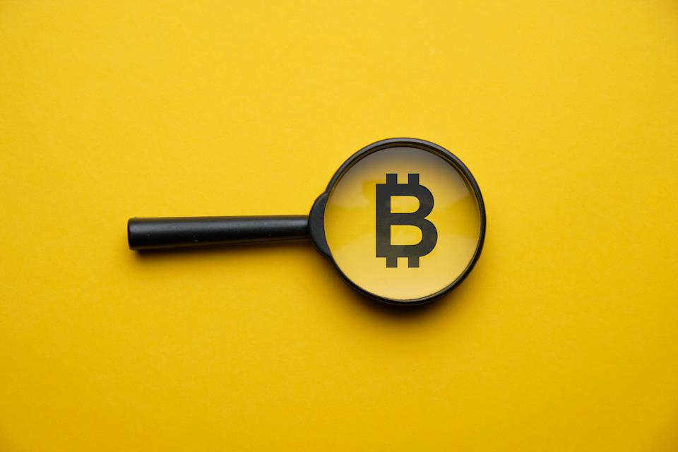 Bitcoin cryptocurrency search concept with magnifying glass on a yellow background. Close up.