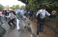 Student protesters run from tear gas fired by riot police during a clash in Jakarta, Indonesia, Monday, Sept. 30, 2019. Thousands of Indonesian students resumed protests on Monday against a new law they say has crippled the country's anti-corruption agency, with some clashing with police.(AP Photo/Achmad Ibrahim)