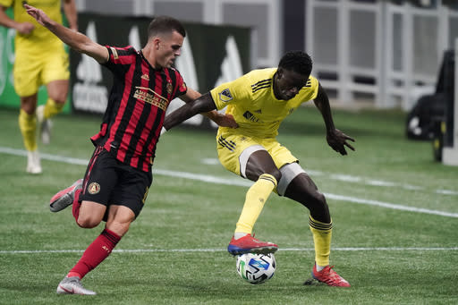 Atlanta United defender Brooks Lennon, left, and Nashville SC forward David Accam vie for the ball during the first half of an MLS soccer match Saturday, Aug. 22, 2020, in Atlanta. (AP Photo/Brynn Anderson)