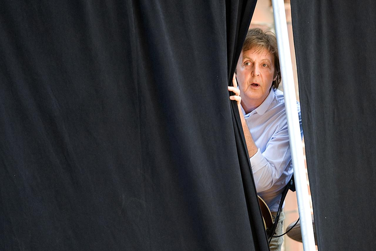 "FILE - In this Wednesday, July 15, 2009 file photo Paul McCartney peeks through the curtains during rehearsals for a performance atop the Ed Sullivan Theater marquee during a taping of ""The Late Show with David Letterman"" in New York. McCartney turned 70 years of age Monday June 18, 2012. (AP Photo/Charles Sykes)"