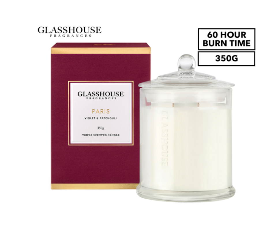 A product image of a Violet and Patchouli scented Glasshouse candle with a red gift box.