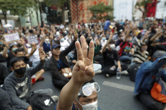 Pro-democracy protesters flash the three-finger protest salute during an anti-government rally at a major intersection in Bangkok, Thailand, Wednesday, Nov. 18, 2020. Police in Thailand's capital braced for possible trouble Wednesday, a day after a protest outside Parliament by pro-democracy demonstrators was marred by violence that left dozens of people injured. (AP Photo/Sakchai Lalit)