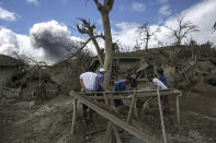 In this Jan. 14, 2020, photo, men recover items on Taal volcano island as it continues to spew ash in Talisay, Batangas province, southern Philippines. So far no one has been reported killed in the eruption, but the disaster is spotlighting the longstanding dilemma of how the government can move settlements away from danger zones threatened by volcanoes, landslides, floods and typhoons in one of the world's most disaster-prone countries. (AP Photo/Basilio Sepe)