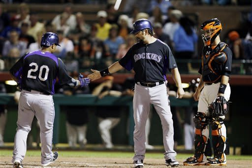 Colorado Rockies' Wilin Rosario (20) is met at the plate by Todd Helton, center, as San Francisco Giants catcher Buster Posey watches following Rosario's two-run home run during an exhibition spring training baseball game, Thursday, March 21, 2013, in Scottsdale, Ariz. (AP Photo/Marcio Jose Sanchez)