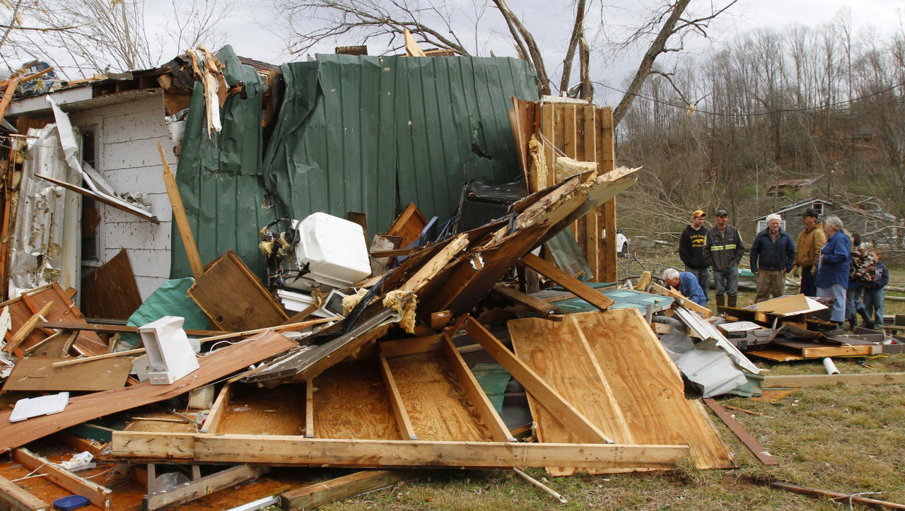 The Shanes family searches through debris of their families home after a tornado ripped through early  Wednesday morning Jan. 30,2013, destroying several homes and businesses in Coble, Tenn. (AP Photo/Butch Dill)
