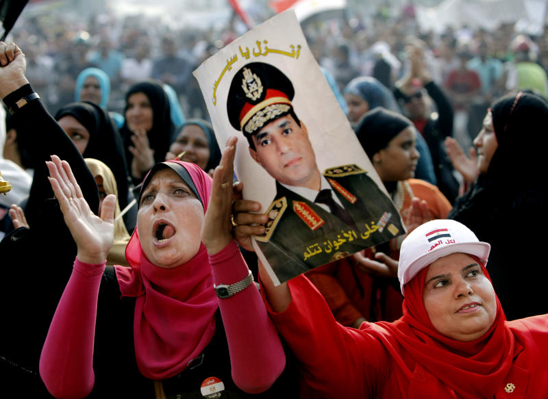 """FILE - In this Monday, July 8, 2013 file photo, Egyptians chant slogans as they hold a poster of Egyptian Army Chief Lt. Gen. Abdel-Fattah el-Sissi during a protest in Tahrir Square in Cairo, Egypt. Arabic reads on the poster reads, """"Sissi, go down, let the Brotherhood hide."""" In dark sunglasses and a uniform studded with medals, Egypt's top general is everywhere, looking down from posters and banners proclaiming him """"lion of the nation."""" Adoring songs vow """"We are behind you."""" Barely a month after he removed the elected president, Gen. Abdel-Fattah el-Sissi is riding a wave of adulation _ in part, state fueled _ that is drawing comparisons between him and modern Egypt's first charismatic strongman, Gamal Abdel-Nasser. Some are warning that the personality cult could pave the way to new authoritarianism. (AP Photo/Amr Nabil, File)"""