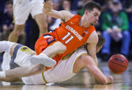 Syracuse's Joseph Girard III(11) competes for a loose ball with Notre Dame's Rex Pflueger during the first half of an NCAA college basketball game Wednesday, Jan. 22, 2020, in South Bend, Ind. (AP Photo/Robert Franklin)