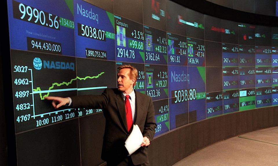 More than a year before the dot-com bubble burst, former CNN correspondent Charles Molineaux delivers a live broadcast from the Nasdaq MarketSite in Times Square, showing the Nasdaq composite index soaring to its first close above 5,000 - Credit: AP