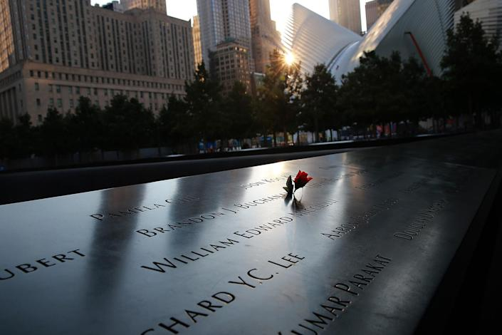 <p>A flower is laid on the panels of the names of victims from the Sept. 11, 2001, attacks are reflected by the morning light on Sept. 8, 2016. (Gordon Donovan/Yahoo News) </p>
