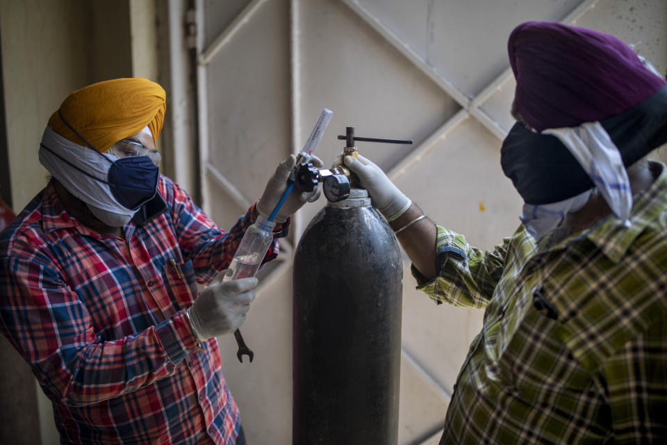 Volunteers from a Gurdwara, a Sikh place of worship, prepare oxygen cylinders for patients in New Delhi, India, Saturday, April 24, 2021. India's medical oxygen shortage has become so dire that this gurdwara began offering free breathing sessions with shared tanks to COVID-19 patients waiting for a hospital bed. They arrive in their cars, on foot or in three-wheeled taxis, desperate for a mask and tube attached to the precious oxygen tanks outside the gurdwara in a neighborhood outside New Delhi. (AP Photo/Altaf Qadri)