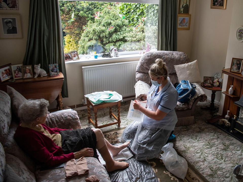 <p>District nurse Rebecca McKenzie changes the dressings on the legs of 86-year-old Margaret Ashton to treat her leg ulcers during a home visit in Grimsby, Lincolnshire</p> (PA)