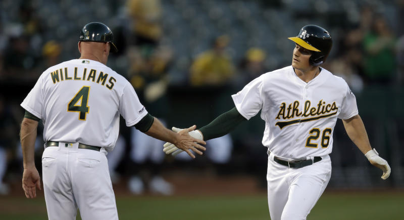 Oakland Athletics' Matt Chapman, right, is congratulated by third base coach Matt Williams (4) after hitting a home run off Texas Rangers pitcher Lance Lynn in the first inning of a baseball game Tuesday, April 23, 2019, in Oakland, Calif. (AP Photo/Ben Margot)