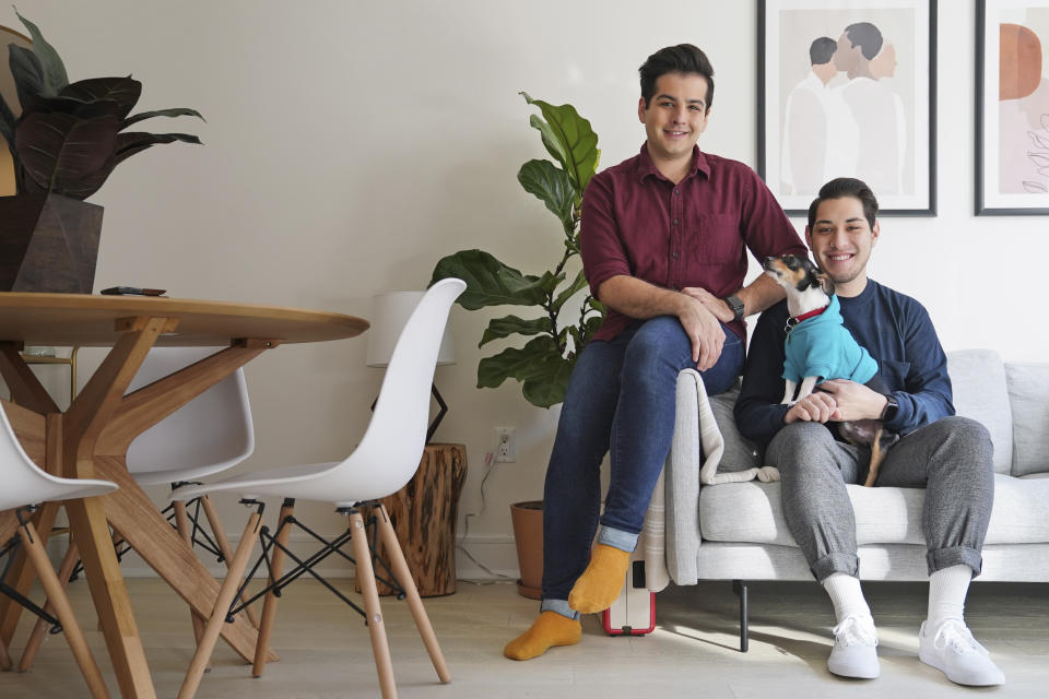 Zachariah Mohammed, left, Pete Mancilla, and their dog Remy pose for a picture in their apartment in New York. Most of the furniture in their apartment, including the couch, the table and chairs, the side table and the bar cart, are rented. (AP Photo/Seth Wenig)