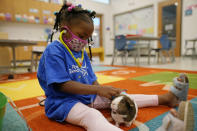 A Pre-K student plays with the class guinea pig, at Positive Tomorrows, Tuesday, Aug. 17, 2021, in Oklahoma City. Positive Tomorrows, an Oklahoma City school exclusively for students in families experiencing homelessness, received money from Gov. Kevin Stitt's Stay in School program and forgivable Paycheck Protection Program loans from the federal government. (AP Photo/Sue Ogrocki)