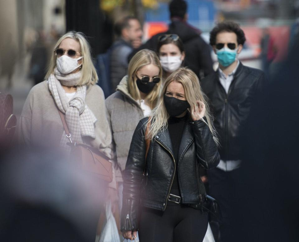 "<span class=""caption"">People wear face masks to help control the spread of COVID-19 as they walk along a street in Montréal on Oct. 18, 2020.</span> <span class=""attribution""><span class=""source"">THE CANADIAN PRESS/Graham Hughes</span></span>"