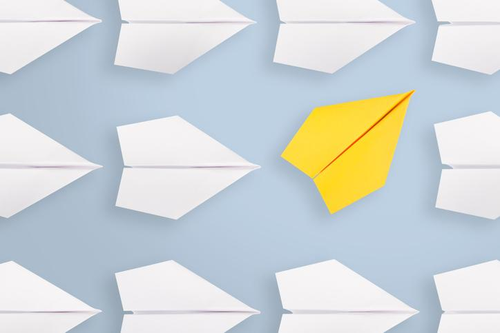 A yellow paper airplane moving in a different direction than many white paper airplanes nearby.