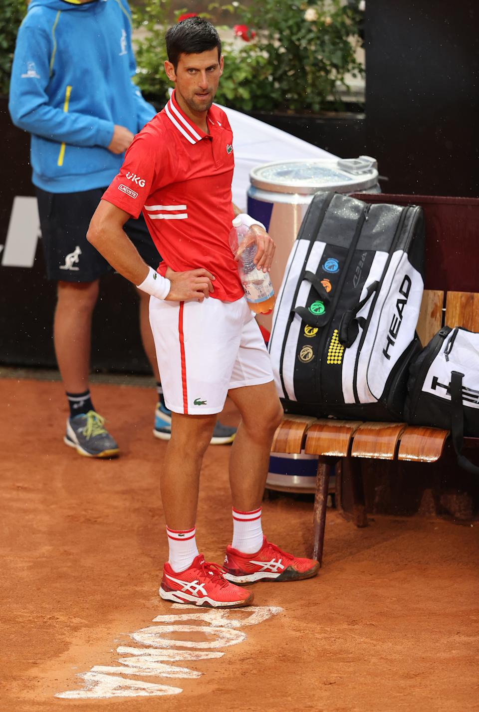 Novak Djokovic  waits to see if the umpire will stop the match due to heavy rain whilst playing Stefanos Tsitsipas during their match on Day Seven of the Internazionali BNL D'Italia at Foro Italico on May 14, 2021.