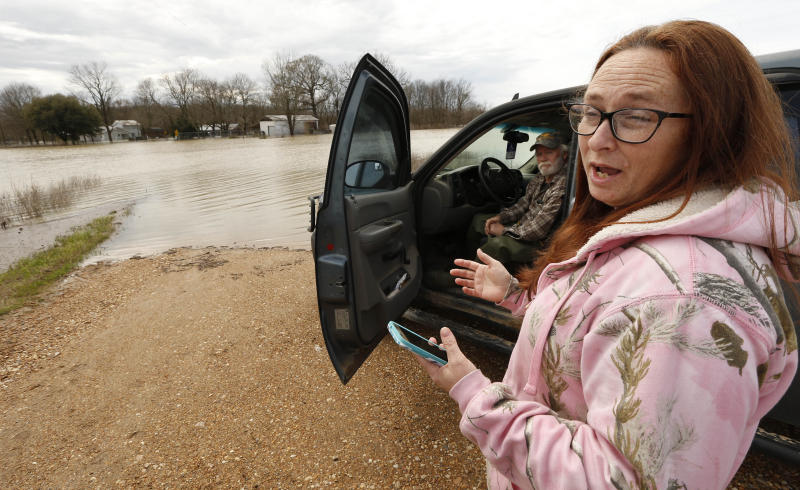 "In this Monday, March 11, 2019 photo, Peggy and her husband George Sellars sit by the ""lake"" that was the driveway to their home, along Mississippi 16, east of Rolling Fork, Miss. The couple said the backwater flooding is the worse they have encountered and correctly concluded that water would overtop the retention levee that protected their house and three others. This week the Federal Emergency Management Agency (FEMA), the Mississippi Emergency Management Agency (MEMA), along with select local emergency management offices will be conducting joint damage assessments in response to the severe storms and flooding are impacting the state. (AP Photo/Rogelio V. Solis)"