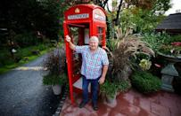 """Gary Blackburn, a 53-year-old tree surgeon from Lincolnshire, Britain, is posing in front of his original British telephone box previously located at Trafalgar Square in London at his British curiosities collection called """"Little Britain"""" in Linz-Kretzhaus, south of Germany's former capital Bonn, Germany, August 24, 2017. REUTERS/Wolfgang Rattay"""