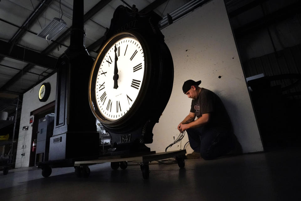 Electric Time technician Dan LaMoore lights up a two-dial Howard Post Clock, Tuesday, March 9, 2021, in Medfield, Mass. Daylight saving time begins at 2 a.m. local time Sunday, March 14, 2021, when clocks are set ahead one hour. (AP Photo/Elise Amendola)
