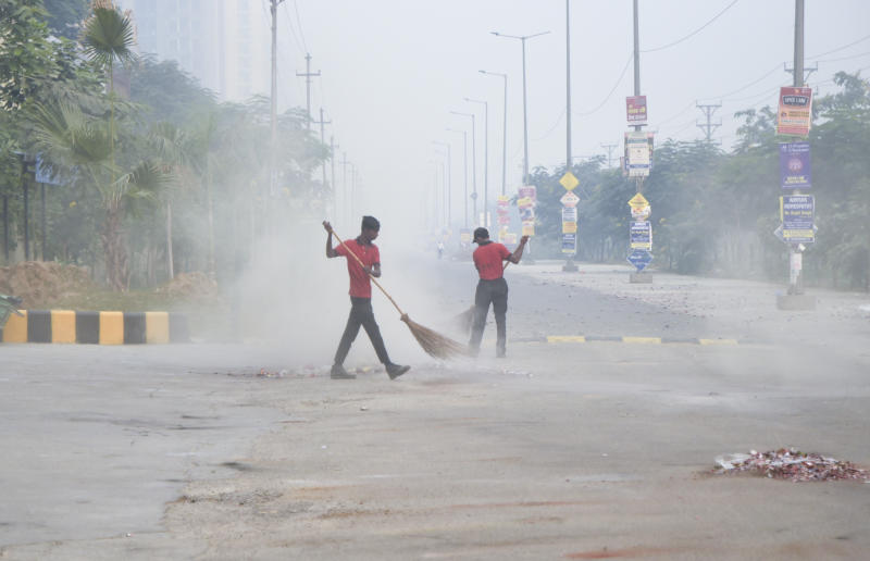Indian workers are seen in the morning smog as they clean a lane littered with remains of firecrackers set off Wednesday night in Greater Noida, near New Delhi, India, Thursday, Nov.8, 2018. Toxic smog shrouded the Indian capital as air quality plummeted to hazardous levels Thursday after tens of thousands of people set off a multitude of firecrackers to celebrate the major Hindu festival of Diwali. (AP Photo/R S Iyer)