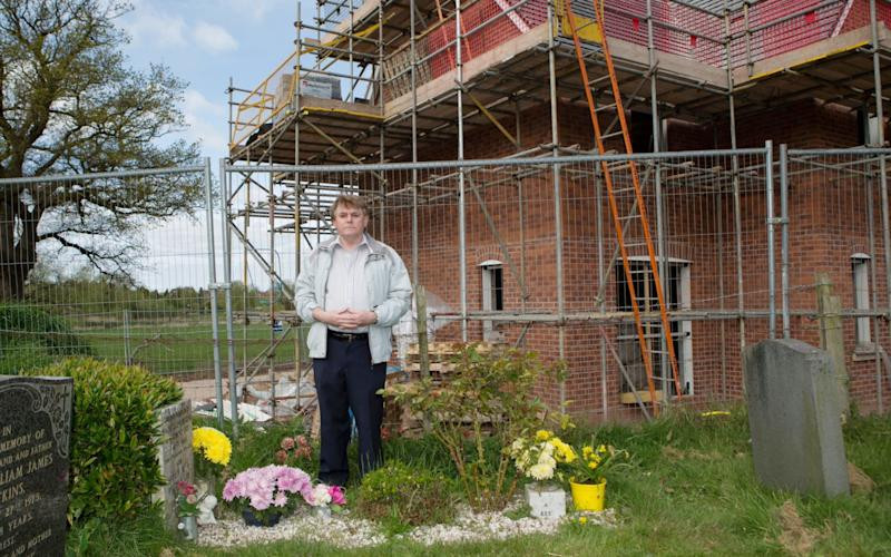 Bill Higgins who is not happy about a new housing estate being built just inches from his parents Irene and Morris graves - SWNS.com
