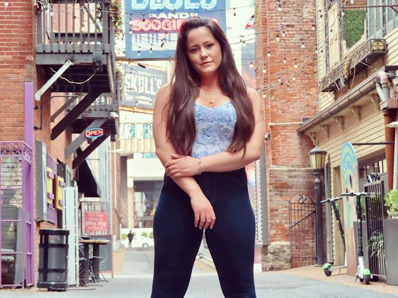 Jenelle Evans poses in a street wearing yoga pants