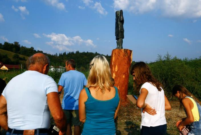 People look at the new bronze statue of U.S. first lady Melania Trump in Rozno, near her hometown of Sevnica