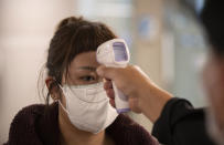 Health officials check tourists' temperatures on arrival in hopes of containing the spread of the COVID-19 virus at the Suvarnabhumi Airport in Bangkok, Thailand, Wednesday, March 4, 2020. (AP Photo/Sakchai Lalit)