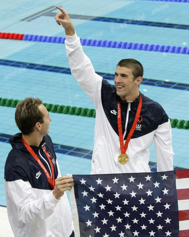 United States' Aaron Peirsol, left, and Michael Phelps hold up their country's flags after the medal ceremony of the men's 4x100m medley relay in which they won the gold, during the swimming competitions in the National Aquatics Center at the Beijing 2008 Olympics in Beijing, Sunday, Aug. 17, 2008. (AP Photo/Itsuo Inouye)