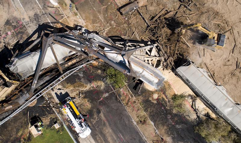 Crews work the site of a train derailment and bridge collapse at the Salt River Union Pacific Bridge at Tempe Town Lake on July 30, 2020, in Tempe. The train derailed causing a fire and the bridge's collapse on July 29.