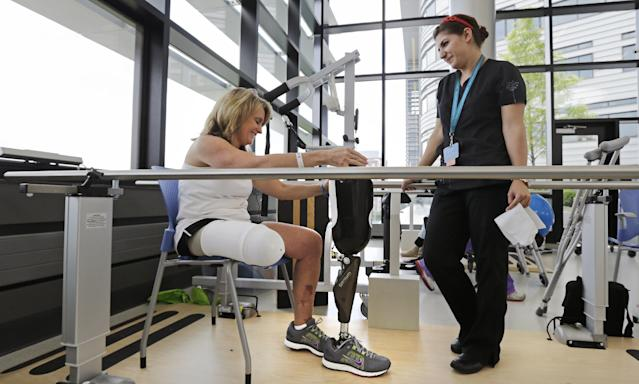 Boston Marathon bombing survivor Roseann Sdoia, of Boston, talks with physical therapist Dara Casparian as she prepares to fit her prosthetic leg at the Spaulding Rehabilitation Hospital, Friday June 20, 2013, in Boston. Sdoia went back to the hospital to learn to walk with her new leg. (AP Photo/Charles Krupa)