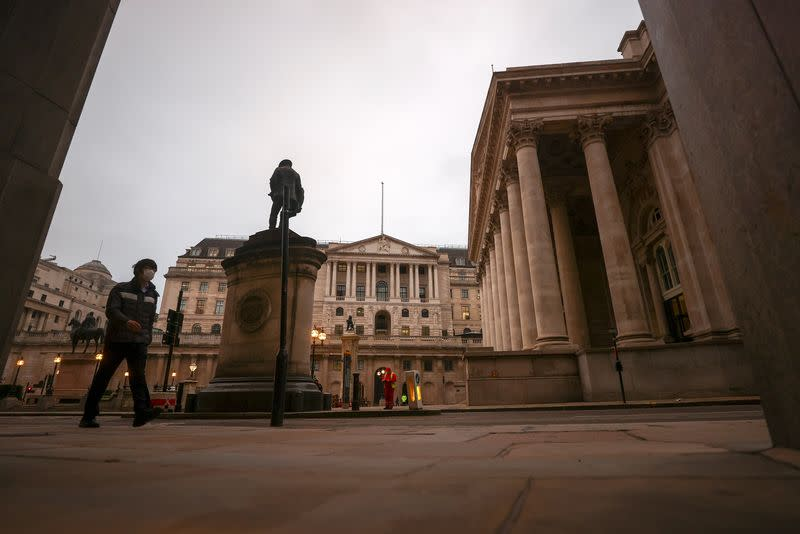 A pedestrian walks past the Bank of England, in London
