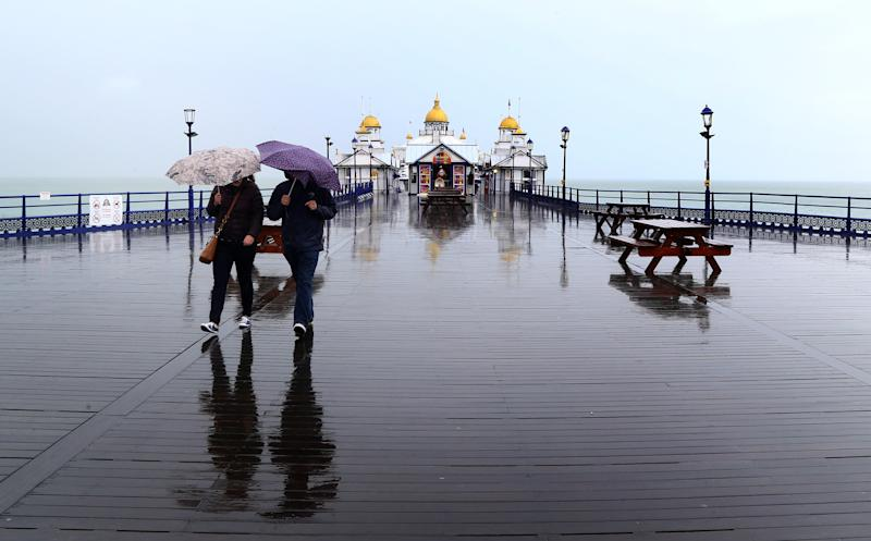 People walk along the pier in Eastbourne, Sussex (Picture: PA)