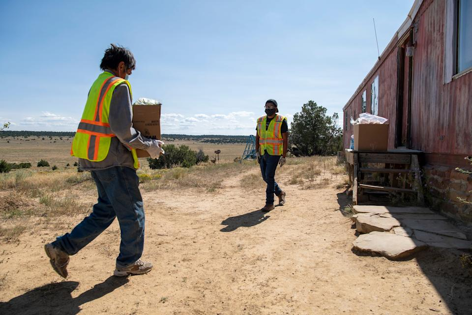David Martine, left, and Vernard Martinez, right, deliver supplies to the home of Gilbert Martinez on the Ramah Navajo Indian Reservation.