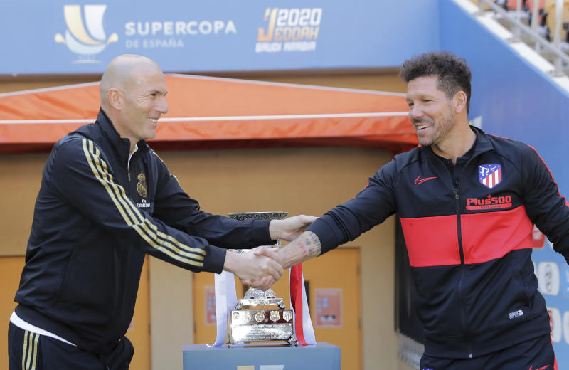 Atletico Madrid's head coach Diego Simone, right, shakes hands with Real Madrid's head coach Zinedine Zidane during the trophy photo call at King Abdullah stadium, in Jiddah, Saudi Arabia, Saturday, Jan. 11, 2020, ahead of their Spanish Super Cup Final soccer match between Real Madrid and Atletico Madrid on Sunday. (AP Photo/Hassan Ammar)