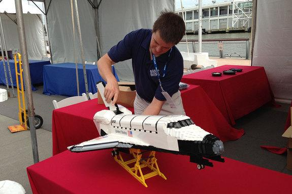"""LEGO """"Master Builder"""" Ed Diment attaches the tail to his LEGO model of space shuttle Enterprise before its debut at the Intrepid Sea, Air and Space Museum in New York, July 26, 2013."""