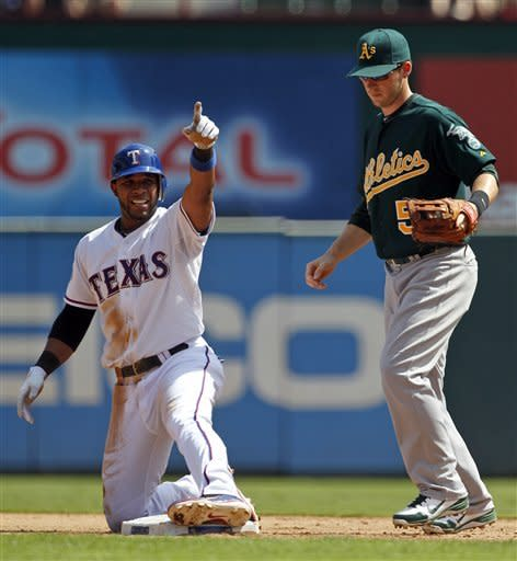 Texas Rangers' Elvis Andrus points to the dugout after doubling to right as Oakland Athletics shortstop Stephen Drew (5) watches in the second inning of a baseball game, Thursday, Sept. 27, 2012, in Arlington, Texas. (AP Photo/Tony Gutierrez)