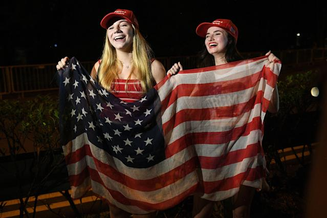 "<p>Erica Boland (R), a US student based in Singapore and a supporter of US President Donald Trump, and her friend wave a US flag as they wait for his arrival, outside the Shangrila hotel in Singapore on june 10, 2018. – Kim Jong Un and Donald Trump will meet on June 12 for an unprecedented summit in an attempt to address the last festering legacy of the Cold War, with the US President calling it a ""one time shot"" at peace. (Photo by TED ALJIBE / AFP) (Photo credit should read TED ALJIBE/AFP/Getty Images) </p>"