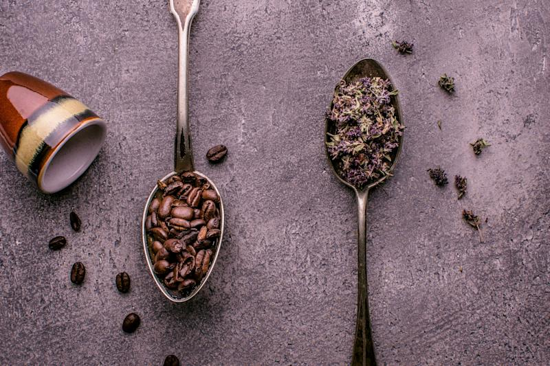 Coffee Beans and Tea in Rustic Spoons over Dark Stone Background