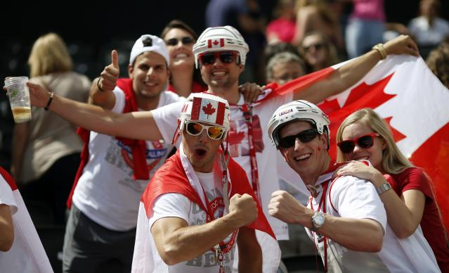 Fans of Canada pose with their national flag during the men's preliminary round beach volleyball match between Canada and Norway at the London 2012 Olympic Games at Horse Guards Parade July 30, 2012. REUTERS/Marcelo Del Pozo (BRITAIN - Tags: SPORT VOLLEYBALL SPORT OLYMPICS)