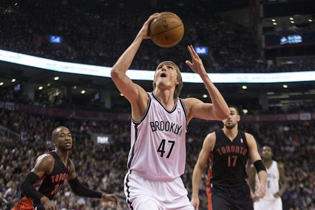 Brooklyn Nets forward Andrei Kirilenko (47) shoots as Toronto Raptors' Terrence Ross, left, and Jonas Valanciunas look on during the first half of an NBA basketball game, Saturday, Jan. 11, 2014 in Toronto (AP Photo/The Canadian Press, Chris Young)