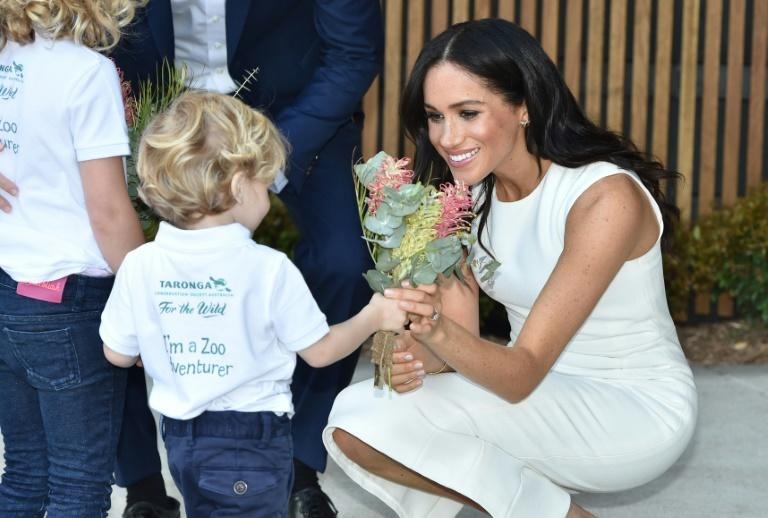 Strike a posie: Meghan has been presented with gifts at every turn from people young and old