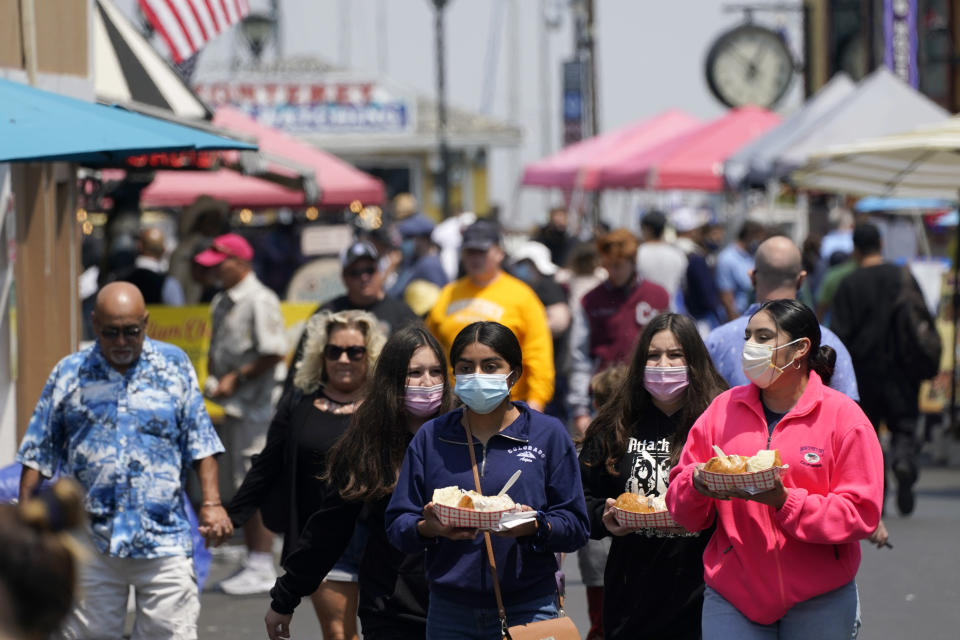 FILE— In this Aug. 9, 2021 file photo people walk along Fisherman's Wharf in Monterey, Calif. Sept. 14 is the last day California voters can cast their ballots to either keep California Gov. Gavin Newsom or recall him and replace him with one of the nearly four dozen candidates seeking to replace him. But today's California electorate is less Republican and more Asian and Latino than it was 18 years ago, trends that favor Newsom. (AP Photo/Rich Pedroncelli, File)